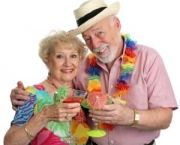 An attractive senior couple on vacation drinking tropical drinks with little umbrellas.  Isolated.